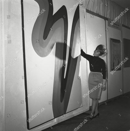 """An example of contemporary art at the National Arts and Antiques Festival at New York's Madison Square Garden, is looked over by Lesley Gore, young recording artist, . The painting, by Nadia Gould, is titled """"Because I'm Young, Beautiful and Talented."""" Mrs. Gould's husband, Philip Gould, is Lesley's art teacher at Sarah Lawrence College"""