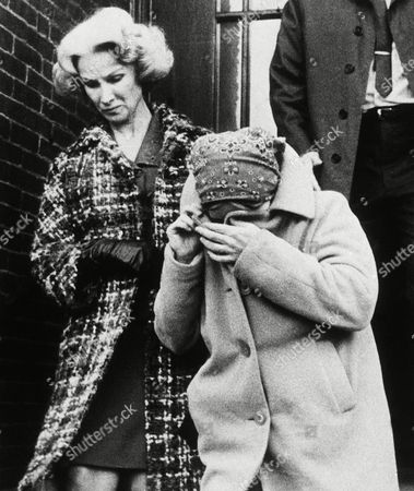 Linda Kasabian, right, covers her face as Los Angeles Police woman Joan Simpson escorts her from Court House to start the trip back to California, Concord, N.H. The twenty-year-old girl was arrested in New Hampshire yesterday on a fugitive warrant for Los Angeles police who want to question her in connection with the murder of Sharon Tate and others
