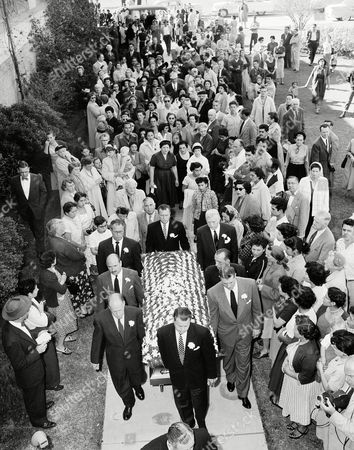 Scores of fans follow the flower-covered casket of actor Lionel Barrymore into Calvary Cemetery Chapel in Los Angeles