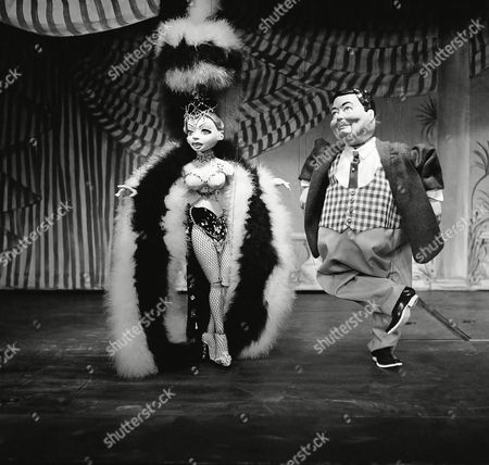 """Puppet version of Jackie Gleason on stage with puppet showgirl in """"Les Poupees de Paris"""" on . Other folk featured in the puppet show include; Maurice Chevalier, Mae West, Liberace, Charles Boyer, Charlie McCarthy, Edie Adams, Jane Kean and Mme. Foster"""