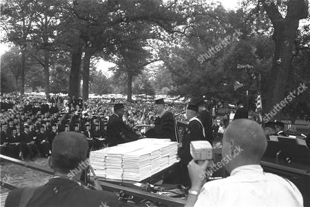 James H. Meredith is shown today receiving his diploma on the stage at the University of Mississippi, . Presenting the diploma is Ole Miss Chancellor, Dr. J. D. Williams. Meredith is the first black man in the school's history to attend and receive a degree. Ceremonies were held in a grove not far from where rioting took place last year when he became the first black to enter the all white school