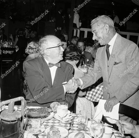Restaurateur Mike Romanoff aka Harry Gerguson with actor Walter Brennan, at left sitting, on