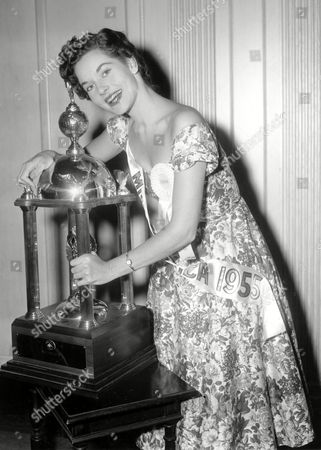 Stock Photo of Meriwether Lee Ann Meriwether, of San Francisco, poses with her trophy on her first day in the role of Miss America 1955 in Atlantic City, N.J., on . The nineteen-year-old won the title last night at the annual Miss America pageant