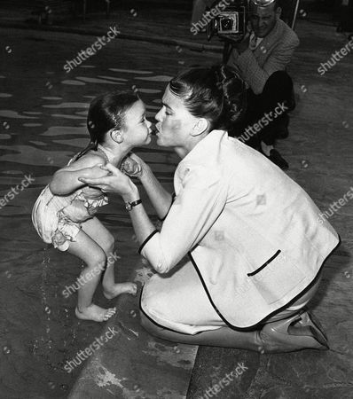 Kathy Crosby, Mary Frances Crosby Two-year-old Mary Frances Crosby, Bing Crosby's only daughter, goes for a swim and gets a kiss from mother, Mrs. Kathy Crosby, right, as she won a Red Cross beginners' swimming card at a Hollywood pool on . Red Cross officials said she is the youngest recipient of the award on record