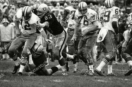 Big Ben Davidson (83) and Tom Keating (on ground) of the Oakland Raiders got to San Francisco 49er quarterback John Brodie on what appeared to be a busted play on in game played on muddy field in Oakland but the play was called back and San Francisco penalized for illegal procedure. The Forty Niner line set a record for the season today when they did not allow the defense to get to the quarterback a single time. Forty Niners also won the game 38-7 and the division championship, their first ever in the NFL