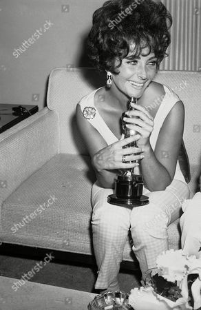 "Actress Elizabeth Taylor holds the Oscar she won as 1960's best film actress for her role in ""Butterfield 8,"" while speaking with reporters in Hollywood, Calif. Publicist Sally Morrison says the actress died in Los Angeles of congestive heart failure at age 79"