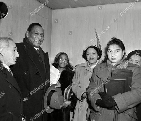 """Singer Paul Robeson, second from left, and unidentified members of a delegation sponsored by the Civil Rights Congress wait in United Nations headquarters to be taken to the offices of Special Service Division Acting Direcor William M. Agar, where they will present a petition charging the U.S. government with """"genocide against the Negro people"""