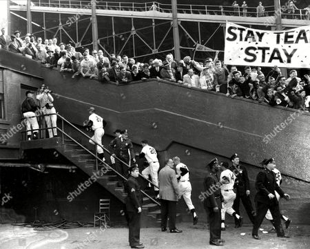 """Members of the New York Giants climb steps to dressing room as fans cheer their team after final game at the Polo Grounds in New York City, . Fans hold a banner urging the Giants to """"Stay Team Stay."""" The players, from left, are, Bobby Thomson (21), Daryl Spencer (20), Whitey Lockman, Gail Harris (14) and Dusty Rhodes (26). The San Francisco-bound Giants lost to the Pittsburgh Pirates, 9-1, in the finale which drew 11,606 persons"""
