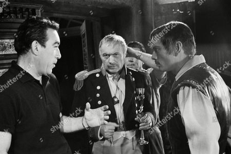 """Anthony Quinn, left, directing his first picture, tells a pair of the best actors in the business how he wants them to play a scene in """"The Buccaneer,"""" . The actors are Charles Boyer, center, and Yul Brynner"""
