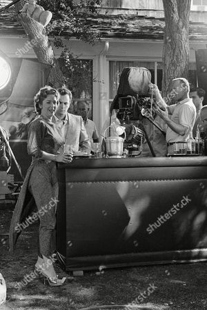 """The facts and foibles of Hollywood, and the people involved - the directors, writers and actors - are related in an upcoming TV play, titled """"Crazy Sunday,"""" an episode in the NBC series, """"The Dick Powell Show."""" Action revolves around the Beverly Hills home of a Hollywood star. Two of the co-stars, Vera Miles and Rip Torn converse at the bar set up outside the house in Beverly Hills"""