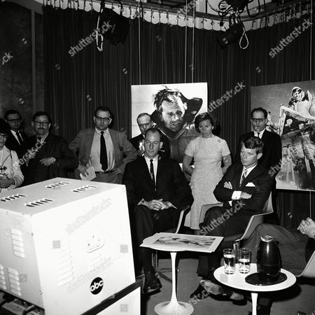 Stock Image of Sen. Robert Kennedy, D-N.Y., narrates the filmed story of his recent climb to summit of Mount Kennedy, at studios of American Broadcasting Company in Washington on . With him is James Whittaker of Seattle,left, who was one of the climbers with Kennedy. Kennedy and Whittaker listen to the playback of tape with Mrs. Ethel Kennedy standing in rear