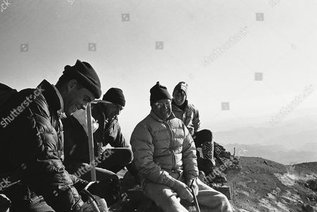Stock Photo of Secretary of Defense Robert McNamara, in white parka, rests at the summit of 14,410-foot Mount Rainier with other members of his climbing party, Mount Rainier, Wash. With McNamara are, Willard Goodwin, left, Dr. Stanley Livingston, next to McNamara, and Craig McNamara, 16, at right. McNamara and his family plan to return to Washington, D.C., leaving tomorrow