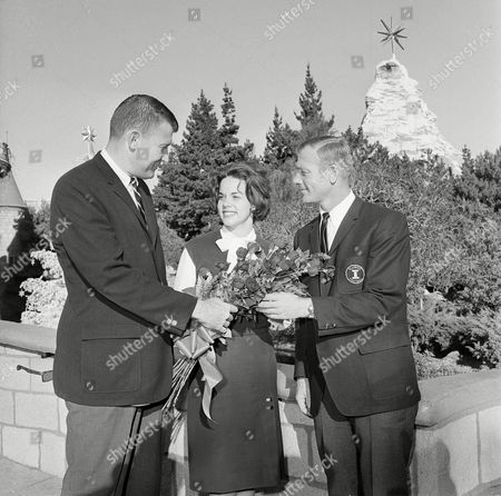 Stock Image of Nancy Kneeland, Jim Owens, Pete Elliott Tournament of Roses Queen Nancy Kneeland gets an assist with her flowers from Washington coach Jim Owens, left, and Illinois coach Pete Elliott during visit to Disneyland in Anaheim, Calif., . Illinois and Washington will meet in the Rose Bowl game Jan. 1, in Pasadena
