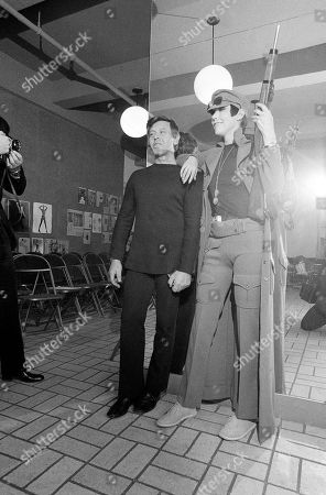Rudi Gernreich Designer Rudi Gernreich, left, presents model Peggy Moffitt wearing a buff-colored knit pants outfit and a matching long coat at a showing of his fashions in New York on . Outfit was enhanced with a toy rifle, G.I. dog tags, boots and a cap