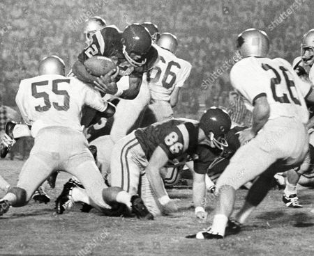 O.J. Simpson, Gregg Field, Bob Miller O.J. Simpson of Southern Cal runs into a couple of Washington State men including Jim Vest (55) in the first period in Los Angeles, and about to fumble the ball. It left his hands as he was dropped, but he managed to recover the fumble himself, picking up only a yard or two on the play. Other identifiable players include Gregg Field (26) of Washington State, and Bob Miller (86) of USC