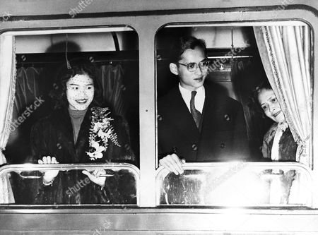 King Bhumibol Adulyadej of Thailand and his wife, 21-year-old Queen Sirikit, leave by Orient Express for Thailand from Lausanne, Switzerland on . At right is the Queen's mother, who came to the railway station to see them off. She will remain in Lausanne. With the King and Queen travelled their seven-month-old daughter, Princess Ubol Ratana, who was born in Switzerland, and a retinue of about 30 persons. The King, who has spent most of his 24 years studying in Switzerland, is now to take up his royal duties permanently. He travelled from Switzerland to Thailand and back again for his coronation ceremony last year. The royal party will board a ship at Genoa