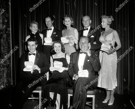 "Holliday Hart Harrison Leighton Tony winners, from left, standing, Judy Holliday, Rex Harrison, Margaret Leighton, Fredric March, Edith Adams, and seated, Sydney Chaplin, Peggy Cass, and Moss Hart pose with their medallions at the 11th Annual Tony Awards ceremony at the Waldorf-Astoria Grand Ballroom in New York City, . Holliday won best actress in a musical for ""Bells Are Ringing""; Harrison won best actor in a musical for ""My Fair Lady""; Leighton won best actress in a dramatic role for ""Separate Tables""; Adams won best supporting or featured actress in a musical for ""Li'l Abner""; Chaplin won best actor in a supporting or featured actor for ""Bells Are Ringing""; Cass won best actress in a supporting or featured dramatic role for ""Auntie Mame""; and Hart won best direction for ""My Fair Lady"