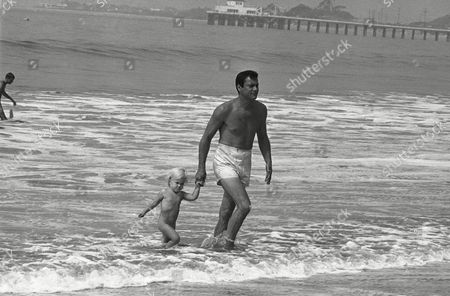 """Alexandra Curtis and her daddy, actor Tony Curtis, in Malibu. The two-year-old, whose mother is actress Christine Kaufmann, was visiting where her father is making a movie, """"Don't Make Waves,"""" when she decided she wanted to go in the water despite lack of a bathing suit"""