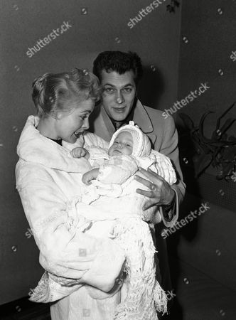 Screen actress Janet Leigh, holding her six-month-old daughter, Kelly Lee Curtis and her husband, actor Tony Curtis have a family reunion at Idlewild Airport, New York on following arrival of the baby from Hollywood. Curtis, at work on a picture in New York, and his wife had their daughter brought from Hollywood to spend the Thanksgiving holiday. A nurse accompanied the baby, who had been staying at the Curtis' California home in her parents' absence