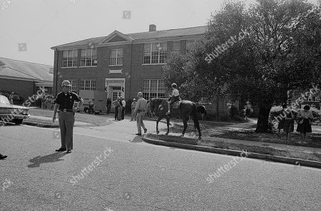 Fourth grade student Lisa Phillips rides the horse of the sheriff's posse on guard at her school in Tuskegee, Ala., . The school, which was to be integrated today, remains closed on orders of Alabama Gov. George Wallace