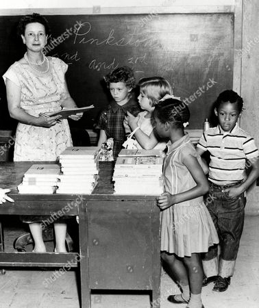 Stock Picture of Mrs. Pinkston enrolls 2nd and 3rd graders at the newly integrated classes at a school in Springer, Okla., . Getting ready to receive supplies are, left to right, Linda Smith, 8; Karita Ellis, 8; Eva Lois Wilson, 7, and Donald James Herndon, 7