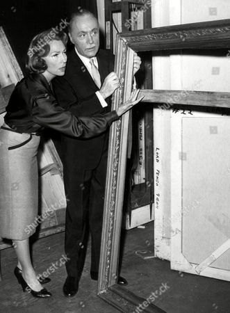 AGNES MOOREHEAD; CHALES BOYER French actor Charles Boyer and American actress Agnes Moorehead, pose next to an empty picture frame at the Royal Theater in New York, USA, the night of, following the performance of the Broadway play 'Lord Pengo', in which they play lead roles. Theater officials reported to police that when stagehands came to work on the set of the play, a copy of the painting 'Aristrotle Contemplating the Bust of Homer' had been neatly cut out from the frame and carried away. The painting is involved in the action of the play, in which Boyer plays 'Lord Pengo', who bears a strong resemblance to a framed art dealer. In order to avoid changes in the play, a different painting was placed upstage, out of the audiences view