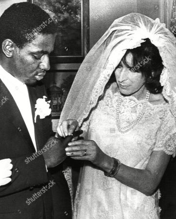 Bride Dawn Langley Hall, whose sex was changed from male to female by surgery, places a ring on her husband's hand, John Paul Simmons, during a private wedding ceremony in Charleston, S.C., on
