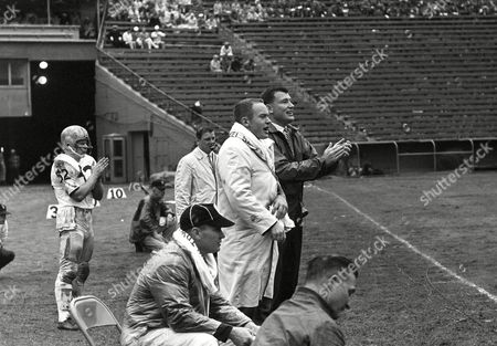Jim Owens, Bob Schloredt Head coach Jim Owens of the University of Washington happily claps his hands as his Huskies rack up a gain against the University of Southern California at the Coliseum in Los Angeles, Calif., . Bob Schloredt, injured Washington quarterback, stands beside him