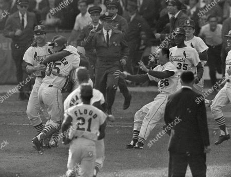 Tim McCarver, Cardinals catcher, embraces hurler Bob Gibson after final out in their 7-5 victory over the Yankees here on in World Series game at St. Louis. Third baseman Ken Boyer is on extreme left. Rishing in at left to congratulate their teammates are Ed Spiezio (26) and Mike Cuellar. In foreground, backs to camera, are Curt Flood and Mike Shannon