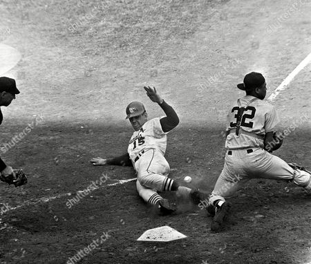 Tim McCarver, Cardinals catcher, scores on double steal in third inning of final World Series game here on at St. Louis. Ball, canter, gets by Yanks catcher Elston Howard. Play started when Cards Mike Shannon, who had singled, and McCarver, on third both took off on double steal. Howard fired to Richardson in attempt to head of Shannon. Bobby Richardsonís return throw was too late