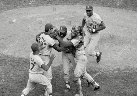 St. Louis Cardinals pitcher Bob Gibson is congratulated by catcher Tim McCarver and third baseman Mike Shannon following his three-hit 7 to 2 victory over the Boston Red Sox to win the 1967 World Series at Fenway Park in Boston, . Also coming in to offer their congratulations is Bob Tolan (17) and Orlando Cepeda