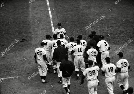 New York Giants converge on pinch-hitter Dusty Rhodes as he comes in to score his 10th inning three-run homer to give the team a 5-2 win over Cleveland in the World Series opener at the Polo Grounds in New York