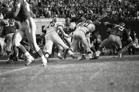 Stock Image of Y.A. Tittle the passer is the natural target for hostile linemen. Here some 755 pounds of Cleveland Browns -- Frank Parker (78) 255, Paul Wiggin (84) 245, Bill Glass (80) 255 -- bear down as Tittle gets off his pass on