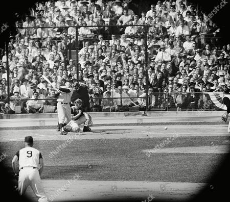 """Edward """"Whitey"""" Ford, New York Yankees pitcher, drives a hard single back to Pittsburgh Pirates pitcher Bob Friend in the second inning of the World Series sixth game, in Pittsburg,scoring Yogi Berra. The catcher for the Pirates is Hal Smith and the umpire is John Stevens"""