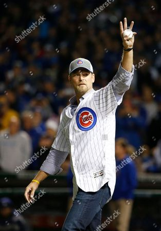 Stock Image of Former Chicago Cubs pitcher Kerry Wood waves before throwing a ceremonial first pitch before Game 6 of the National League baseball championship series between the Chicago Cubs and the Los Angeles Dodgers, in Chicago