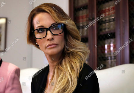 """Jessica Drake, Gloria Allred Jessica Drake listens to a question during a news conference at the office of her attorney, Gloria Allred, in Los Angeles on . Drake, an adult film actress, said Donald Trump kissed her and two other women on the lips """"without asking for permission"""" when they met him after a golf tournament in 2006"""