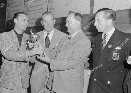 Ben Hogan (left), captain of the U.S. Ryder Cup Team, receives a Gold Golf Trophy from Robert Hudson, sponsor of the Ryder Cup Series on Nov.2, 1947 at Portland, Oregon. The U.S. team defeated the British Ryder Cup team 11 to 1 to retain the trophy. Second from left is Ed Dudley, and at right is Henry Cotton, captain of the British team