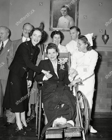 Oksana S. Kasenkina, in wheelchair, Russian school teacher who was injured in a leap from a third floor window of the Russian Consulate in New York, shakes hands with Virginia Muldoon, left, member of the hospital staff, and her nurse, Marion Daly, right, as she prepares to leave Roosevelt Hospital, . Mrs. Kasenkina suffered a leg fracture and other injuries in the leap. In back, left to right, are: Archie O. Dawson, Mrs. Kasenkina's attorney; Nurse Helen Sheppard, and Dr. Eugene Watkins