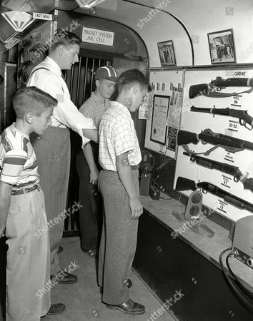 """Jim Fodey, Neal Dorsch, Boyd Niederlander, William Rompe Three Columbus boys look at a model jail cell, with crime prevention equipment, being exhibited in a """"jail on wheels"""" trailer, . William Rompe of New Haven, Conn., describes firearms to, left to right: Jim Fodey, Neal Dorsch and Boyd Niederlander. The Buckeye State Sheriffs Association is sponsoring the Ohio tour to show youngsters that criminals never win"""