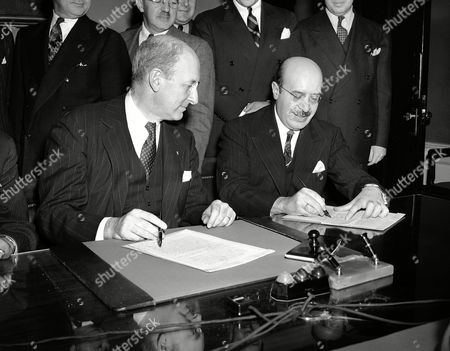 Eduardo Suarez, Henry Morgenthau Eduardo Suarez (right), Mexico's Minister of Finance, sets his signature to a silver agreement between the United States and Mexico at Washington on . Secretary of the treasury Henry Morgenthau (left) contemplates the ceremonies at which pacts settling major disputes between the two nations were effected