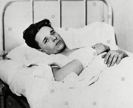 """Francis """"Two-Gun"""" Crowley lies in a bed at the Bellevue Hospital prison ward the morning after his spectacular capture by New York Police in a 90th Street apartment together with Rudolpin Duringer and Helen Walsh, in New York, . Crowley had been shot three times, once in each leg and once in the wrist. None of the wounds were serious. He was later indicted by a Long Island grand jury for the murder of patrolman Frederick Hirsch"""