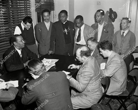 """Benjamin J. Davis Jr., Arthur Wasserman, John Sutton, Bishop E.B. Pulliam, Edward Smith, Charles Griffin, Sam Labon Benjamin J. Davis Jr., seated at left, holds a news conference at the Hotel Theresa on Seventh Avenue and 124th St. in New York City, . Standing are six men who Davis said were involved in a disturbance in Harlem the night of Nov. 3. From left: Arthur Wasserman, John Sutton, Bishop E.B. Pulliam, Edward Smith, Charles Griffin and Sam Labon. Davis condemned the placing of 360 additional police in Harlem after the disturbance as an """"attempt to terrorize the Harlem community"""