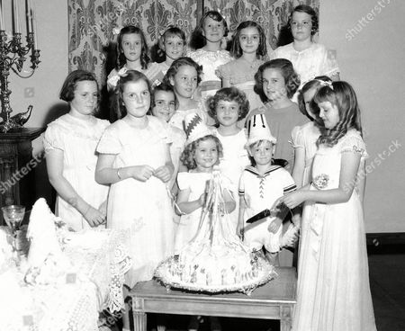 When Gloria Lloyd, right, daughter of the film comedian, Harold Lloyd, celebrated her 11th birthday, the youngest generation of the screen capital turned out en masse in Beverly Hills, Calif., on . There's Shirley Temple, right behind the cake, with Harold Lloyd Jr., (on her left) and Peggy Lloyd (between and behind them), Jane Bannister, daughter of Ann Harding, is on the left end of the back row. All are children of film people