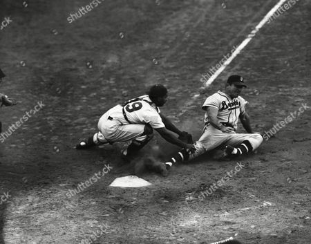 Stock Image of Boston Braves left fielder Jeff Heath, sliding, fractures his left foot (note position) as he slides toward home in the sixth inning of the Boston-Brooklyn Dodger game at Ebbets Field, Brooklyn, New York, . Roy Campanella, Dodgers catcher, tags the runner, and seconds later aides him as he appeared in severe pain. Heath had attempted to score from second on a single by Bill Salkeld. Taken to Swedish Hospital, Brooklyn, it was later announced he had fractured the fibula in the left foot