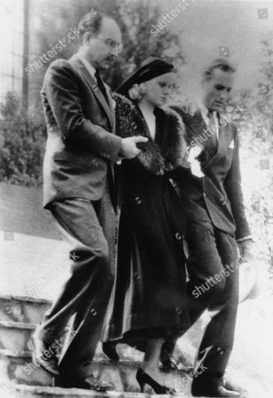 Jean Harlow, Marino Bello, Donald Robertson A tragic figure in black, Jean Harlow, well known actress, is leaving on her step-father, Marino Bello, left, and Donald Robertson, right, leaving the Bello home in Los Angeles for the funeral of her late husband, Paul Bern on