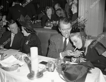 """Jimmy Stewart A dual purpose is served with a match as actor Jimmy Stewart lights a cigarette for Mrs. Hoagy Carmichael during dinner at Ciro's in Hollywood on . """"Light Handed"""" Jimmy not only lit the cigarette, but gave the photographer a chance to check the focus of his camera"""