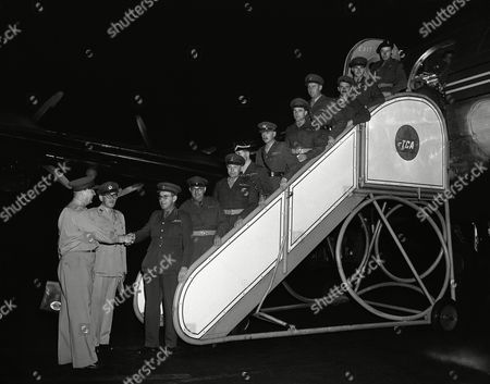 Ten British Army officers, enroute to Japan and Korea, where they plan to make preliminary arrangements for the arrival of United Kingdom troops, are greeted on their arrival at La Guardia Field, New York, by Col. Frederick J. Bairsto, left, British Army officer stationed in New York, and Capt. P.G. Brooke (second from left), British Army embarkation officer in New York. The arrivals, from left to right on ramp, are: Col. Brian Burke, leader of the group; Maj. Donald Grant; Maj. Austin Marshall; Capt. Neil Whitfield; Capt. Desmond Holmes; Capt. Dennis O?Flaherty; Capt. James Pierson; Capt. Peter Bretland; Lt. John Ellis, and Lt. John Hinds