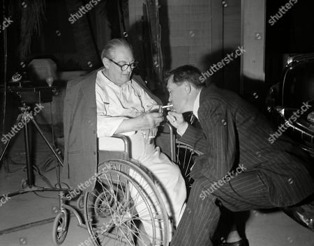 "Actor Lionel Barrymore, in wheelchair, huddles with director John Huston, perched on a car bumper, between scenes during the shooting of ""Key Largo,"" in Hollywood, Calif"