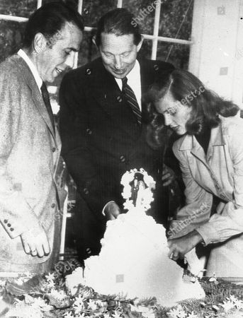 Novelist Louis Bromfield, center, helps actor Humphrey Bogart and his bride, actress Lauren Bacall, cut the cake after their wedding at Bromfield's Malabar Farm near Lucas, Ohio. The couple's oldest child, Stephen Bogart, is helping to raise money to renovate part of Malabar Farm, which is now part of a state park