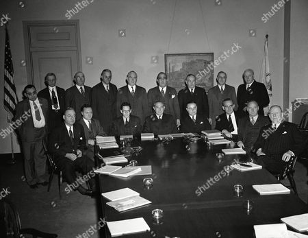 """Members of the Wage Adjustment Board, a """"little war labor board"""" reconstituted by the War Labor Board to handle wage adjustments in the building trades and construction industries as they held their first meeting at the Department of Labor in Washington on . Left to right seated: James D. Marshall, Washington, D.C.; Louis C. Sherman, Washington, D.C. Arthur D. Hill, Jr., Washington, D.C.; D. W. Tracy, Assistant Secretary of Labor and Chairman of the Board; George S. McGahan, Executive Secretary of the Board; Edgar Warren, Washington, D.C.; and Robert Lynch, Washington, D.C.; Standing: John J. McCurry, Washington, D.C.; J.S. Miller, Pittsburgh Penn.; Michael Garrett, Washington, D.C.; Stephen D. Butts, Detroit, Michigan; Paul M. Geary, Washington, D.C.; H. R. Cole, Washington, D.C.; Herbert Rivers, Washington, D.C.; John W. Garvey, Washington, D.C.; Robert Byron, Washington, D.C. and Harry C. Bates, Washington, D.C"""